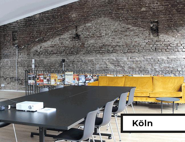 Seminarbereich mit großem Tisch und Sofa vor Backsteinwand